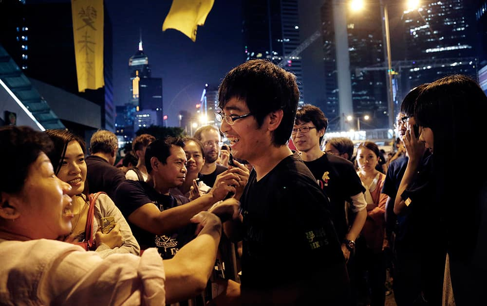 Pro-democracy student leader Alex Chow smiles as supporters encourage him after a rally, in Hong Kong.