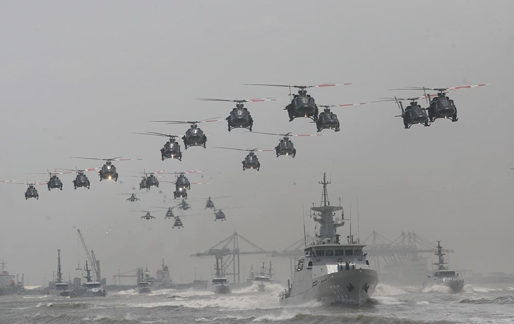 Indonesian Air Force helicopters fly in formation over the fleet of military ships in a show of force during a ceremony commemorating the 69th anniversary of Indonesian Armed Forces in Surabaya, East Java, Indonesia.
