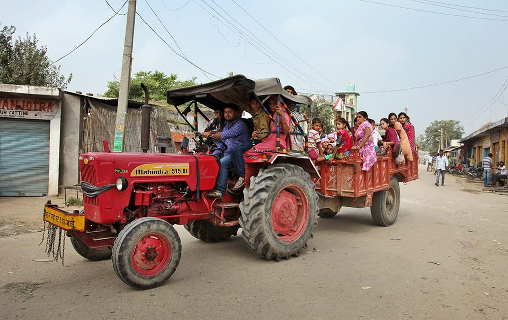 Indian villagers sit in a tractor as they leave their homes for a safer place for fear of firing from Pakistan side of the border in Arnia Sector near the India-Pakistan international border.