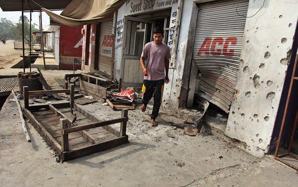 An Indian villager walks near damaged shops hit by mortar attack allegedly fired from the Pakistan's side in Arnia Sector near the India-Pakistan international border.