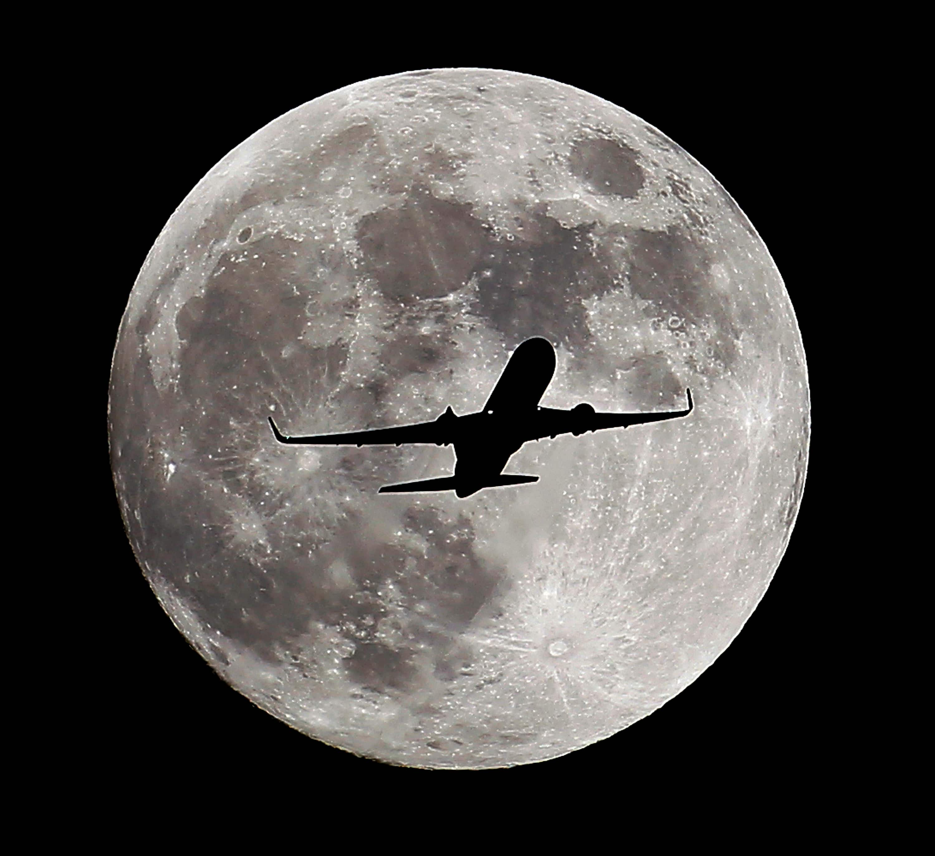 A passenger airliner crosses the full moon, also known as the Hunter's Moon, a few hours prior to the beginning of a total lunar eclipse that will create an effect known as the Blood Moon, in Whittier, Ca.