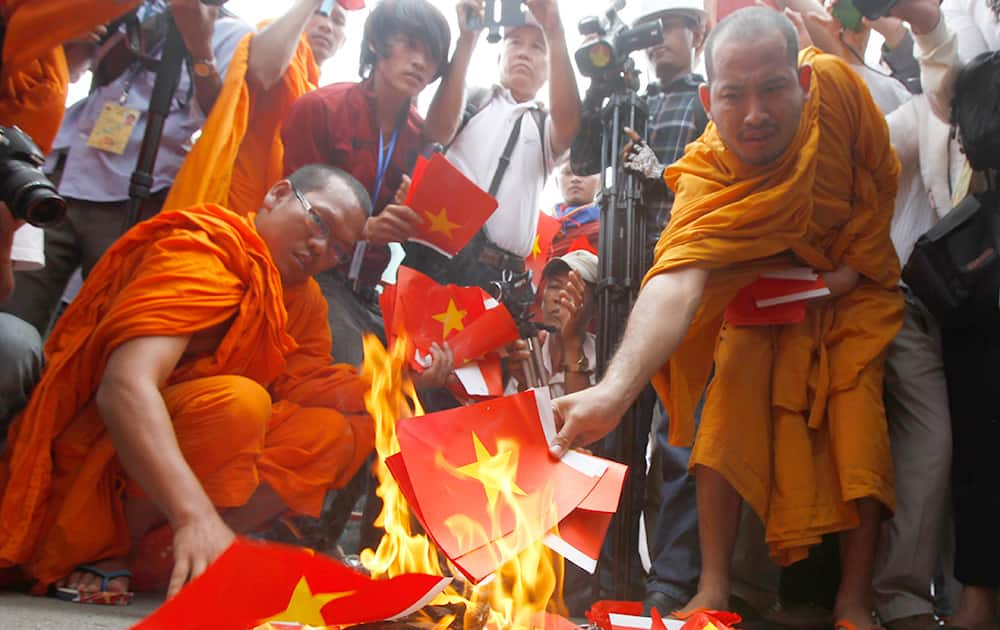Cambodian protesters burn mock Vietnamese flags during a protest at a blocked main street in front of Vietnamese Embassy in Phnom Penh, Cambodia.