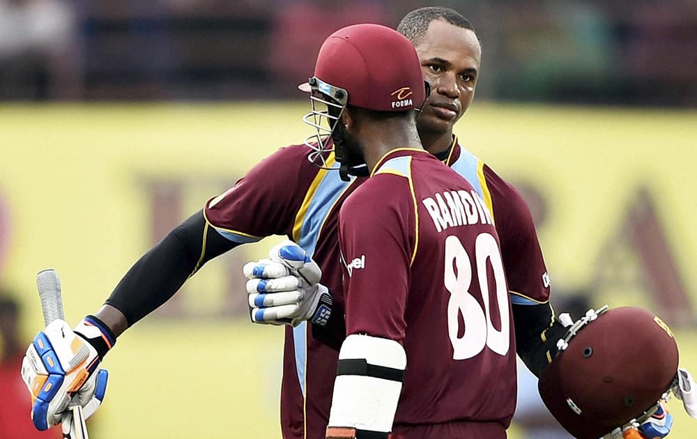 West Indies cricketer Marlon Samuels celebrating his century along with teammate D Ramdin during the first ODI match against India at Jawaharlal Nehru Stadium in Kochi.