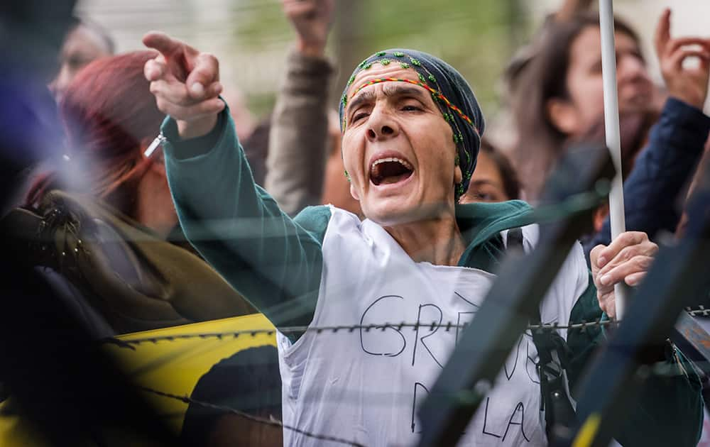 A Kurdish woman living in Belgium shouts slogans as she is on a hunger strike together with other Kurds to protest against the Islamic State militant attacks on the Syrian city of Kobani, in front of the Turkish embassy in Brussels.