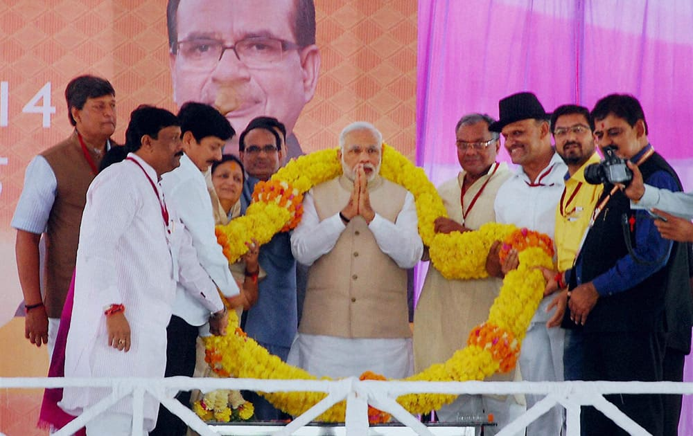 Prime Minister Narendra Modi is garlanded by BJP workers at a party meeting in Indore.