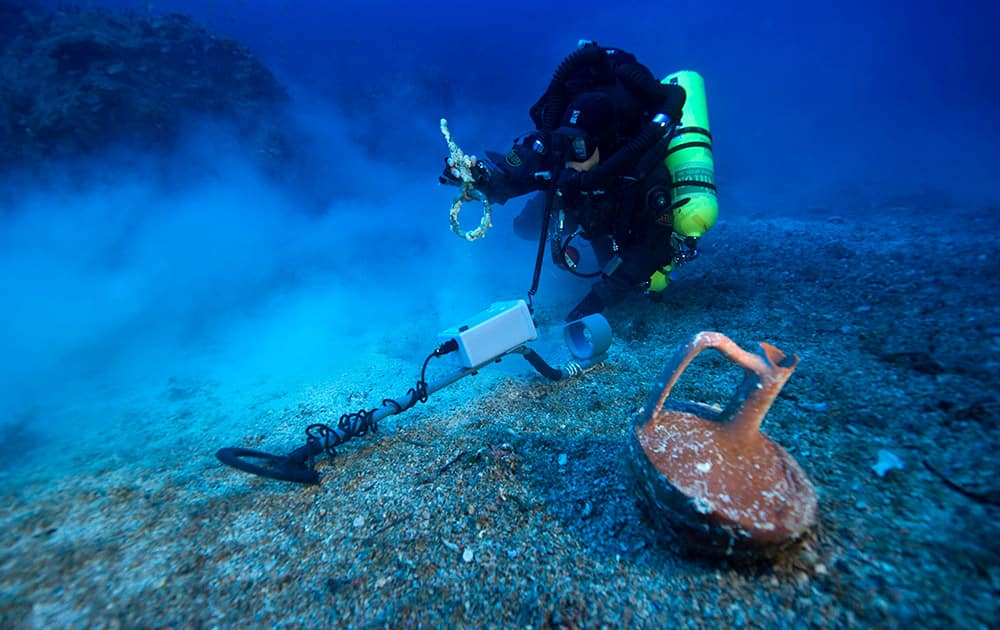 This undated photo provided by Argo via the Greek Culture Ministry, a diver with a metal detector holds a copper ship's fitting next to a vase at the site of the Antikythera wreck off the island of Antikythera in southern Greece.