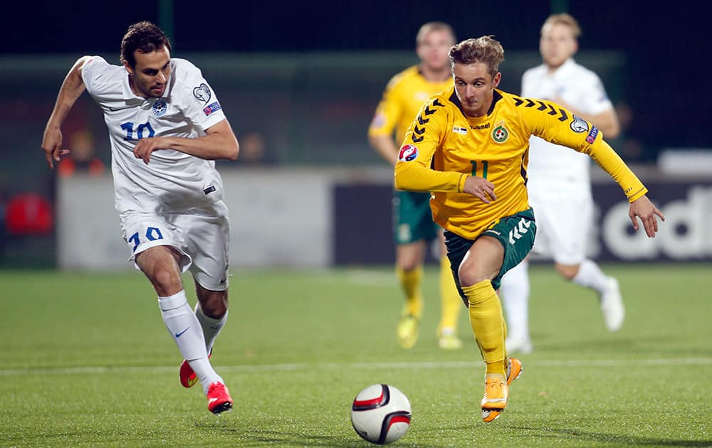 Lithuania's Arvydas Novikovas, right, and Estonia's Sergei Zenjov challenge for the ball during the Euro 2016 soccer qualifying group E match between Lithuania and Estonia in Vilnius, Lithuania.