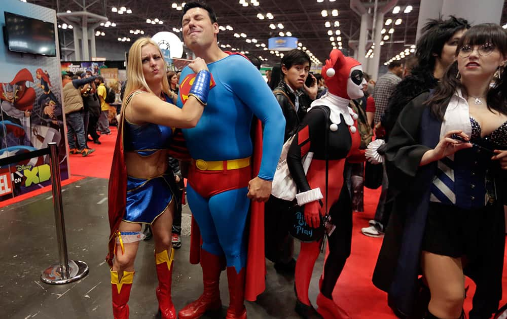 Naomi Harbatuk, left, of Somerset, N.J., dressed as Supergirl, poses with Mike Sullivan, of Ottawa, dressed as Superman during the first day of New York Comic Con at the Javits Convention Center.