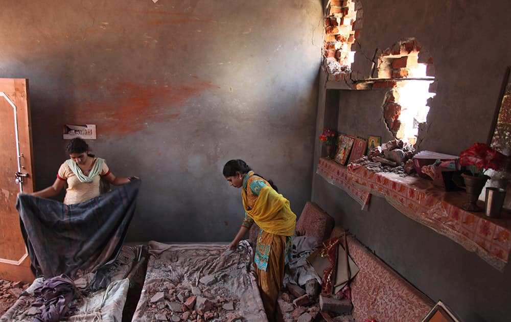 Village women salvage their belongings from one of the houses damaged in firing by Pakistani troops at Village Nanga, in  Jammu and Kashmir.