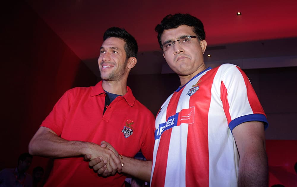 Spanish soccer star Luis Garcia, left poses with former Indian cricket captain and co owner of the Atletico De Kolkata football club of the Indian Super League (ISL) in Kolkata.