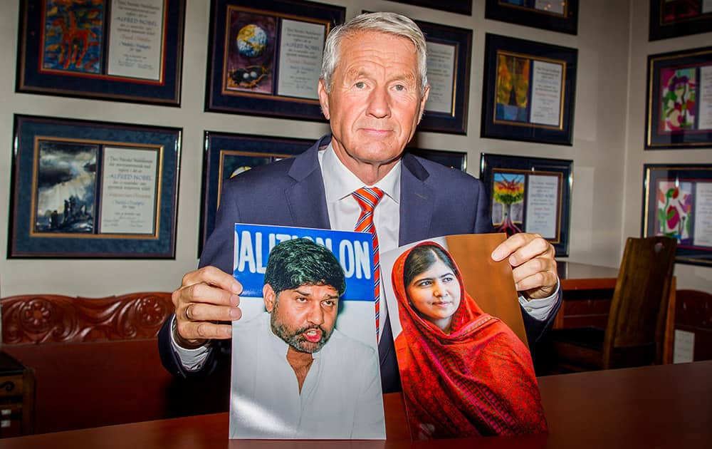 Chair of the Norwegian Nobel Committee, Thorbjorn Jagland holds photos of children's rights activists Malala Yousafzai of Pakistan, right, and Kailash Satyarthi of India at The Norwegian Nobel Institute in Oslo, after they were awarded the Nobel Peace Prize 2014.