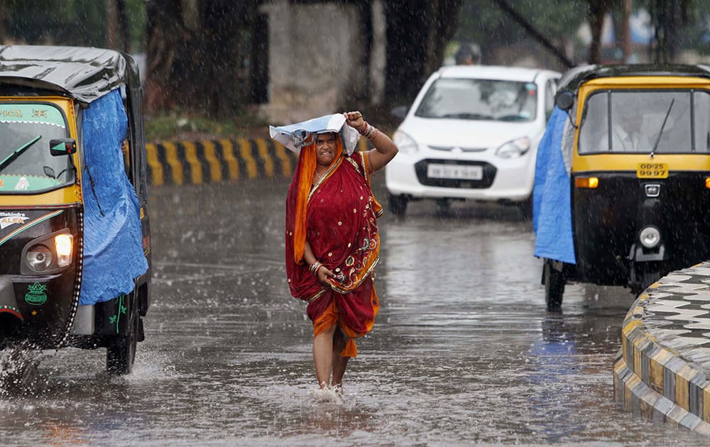 A woman shields herself with a plastic bag as she walks on a road in the rain, in Bhubaneswar. According to Indian Meteorological Department reports, severe cyclonic storm 'Hudhud' is likely to hit Andhra Pradesh and Orissa coasts Sunday.