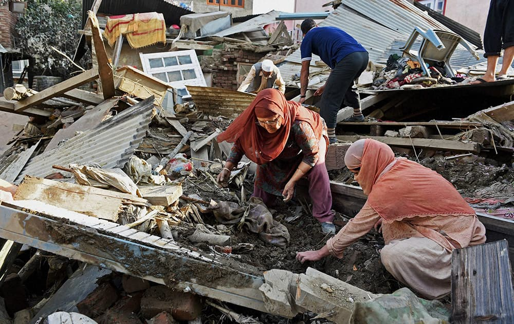 Flood victims salvage their belongings at their collapsed house in Srinagar.