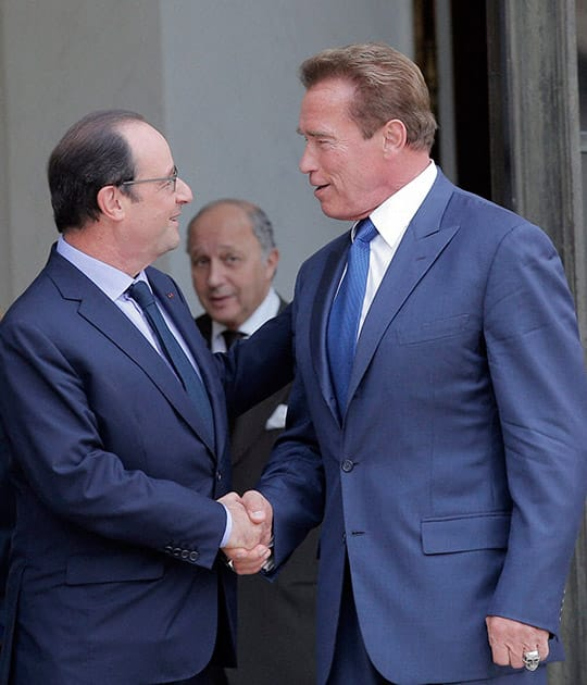 Former Governor of California and founding chair of the R20 initiative, Arnold Schwarzenegger, right, shakes hands with French President Francois Hollande after a meeting at the Elysee Palace in Paris.
