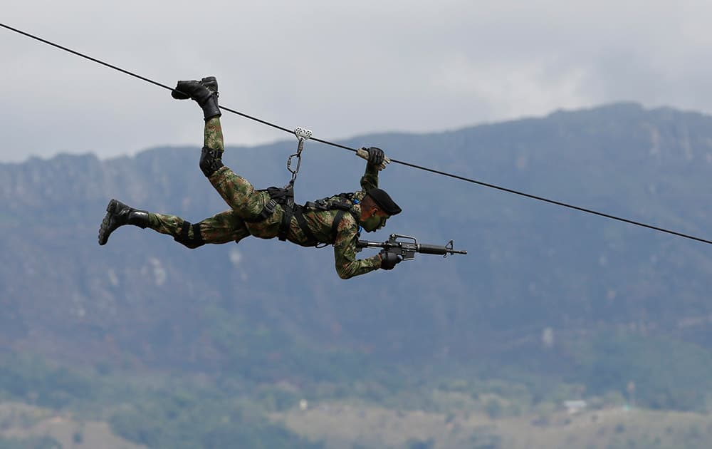 A Colombian Army Special Forces soldier ziplines during a show of military exercises at the Tolemaida military base during a visit by U.S. Defense Secretary Chuck Hagel, in Melgar, Colombia.