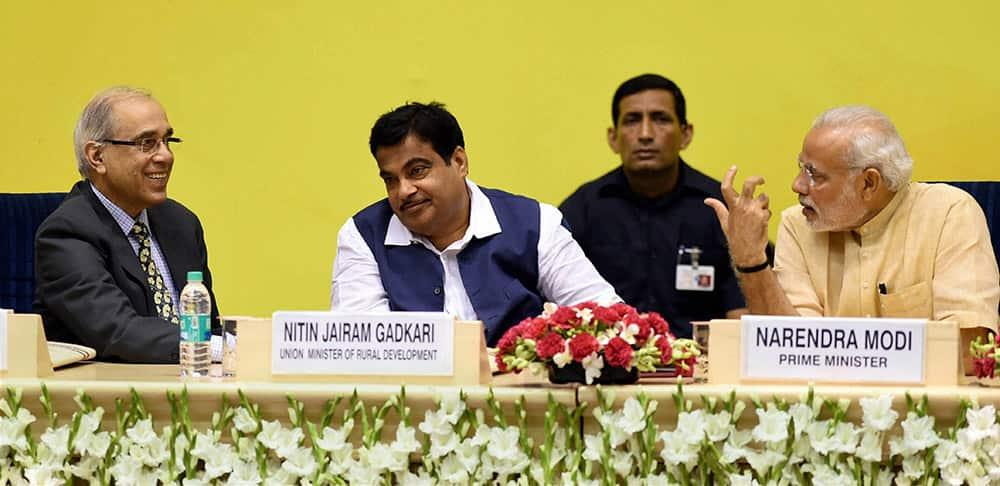 Prime Minister Narendra Modi talking to his Pricipal Secretary Nripendra Misra as Union Minister for Rural Development Nitin Gadkari looks on during the launch of Saansad Adarsh Gram Yojana (SAGY) in New Delhi.