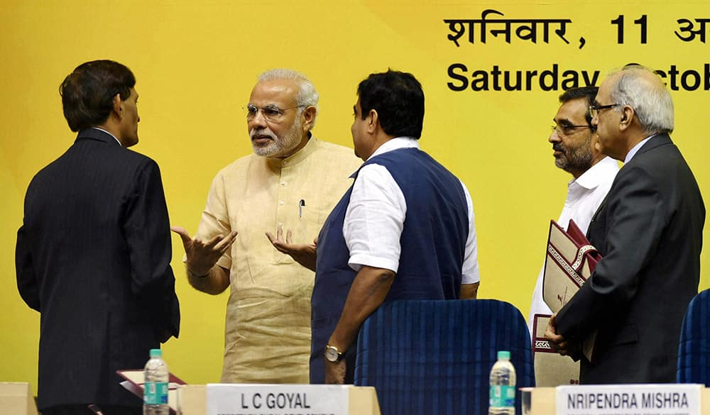 PM Narendra Modi talking to an official as Union Minister for Rural Development Nitin Gadkari and MoS Upendra Kushwaha look on during the launch of SAGY.