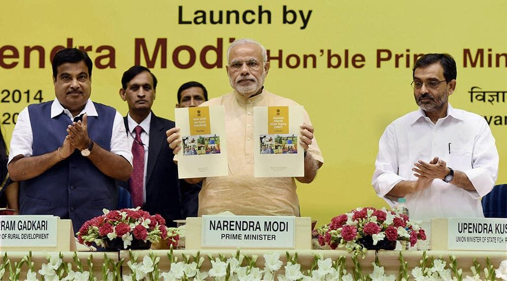 Prime Minister Narendra Modi launches the Saansad Adarsh Gram Yojana (SAGY) as Union Minister for Rural Development Nitin Gadkari and Minister of State for Rural Development Upendra Khushwa clap in New Delhi.