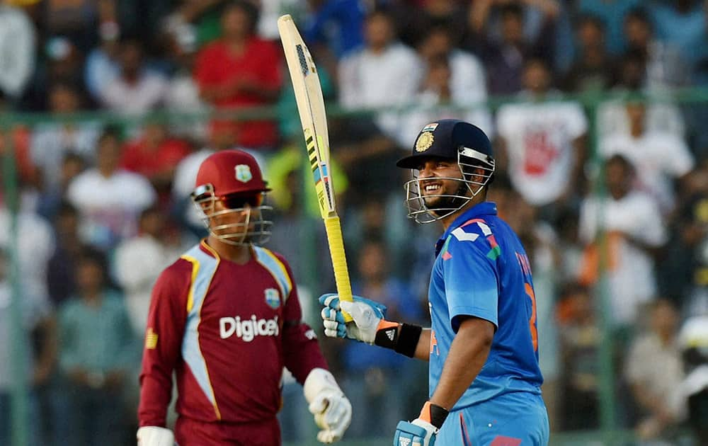 Suresh Raina celebrates his half century against West Indies during the 2nd ODI cricket match in New Delhi.