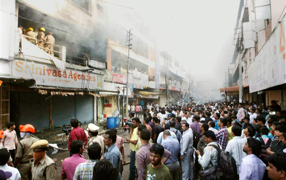 People watch as fire men douse a fire that broke out at a shopping complex in Hyderabad.