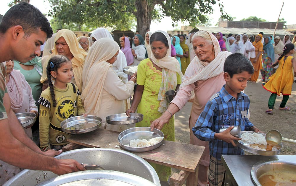 Villagers, who fled from their homes after the exchange of firing between India and Pakistan, receive food ration at an army relief camp at Deoli village, in Arnia.