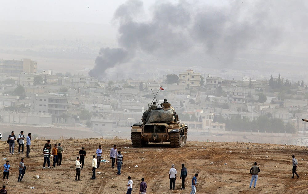Civilians gather to watch fighting between Syrian Kurds and the militants of Islamic State group alongside Turkish soldiers aboard a tank holding a position overlooking the town Kobani, Syria, on a hilltop on the outskirts of Suruc, at the Turkey-Syria border.