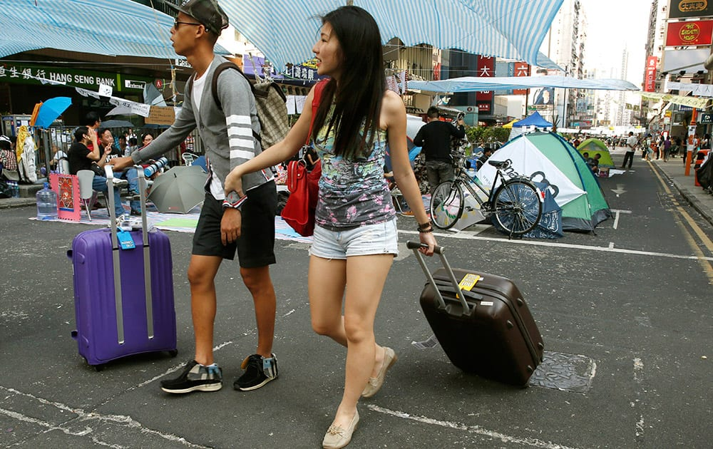 Tourists from Singapore walk on a main road in an area occupied by pro-democracy protesters at Hong Kong's Mongkok district.