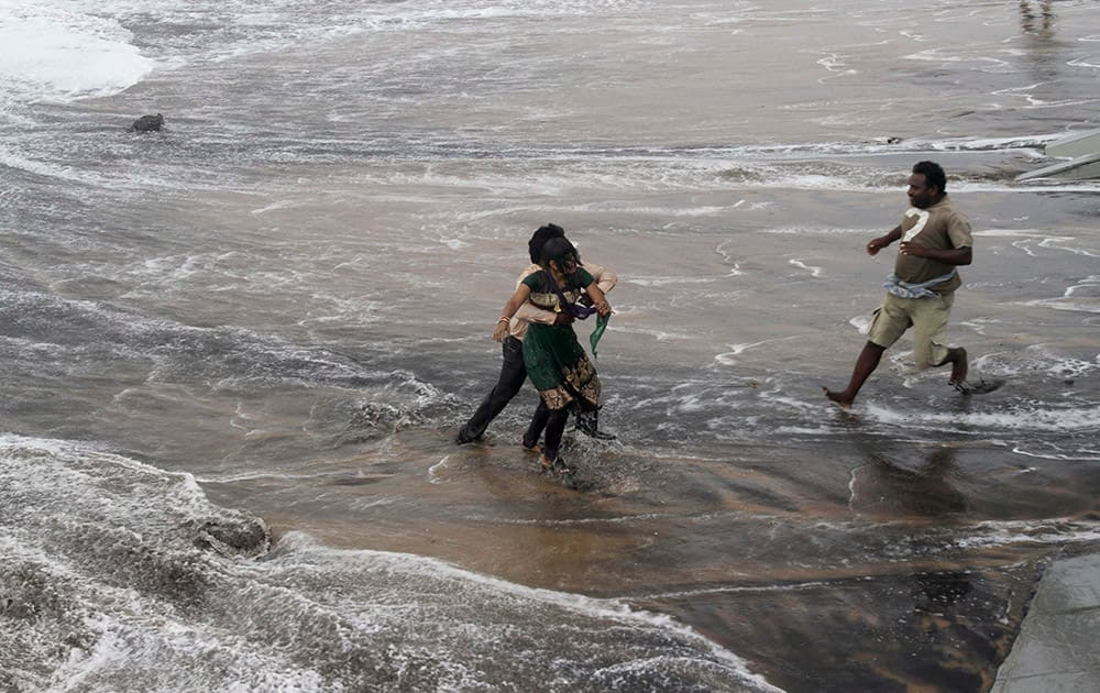 A man, right, rushes to help as another rescues a woman who fell due to strong tidal waves on the Bay of Bengal coast at Gopalpur, Orissa, about 285 kilometers (178 miles) north east of Visakhapatnam, India.