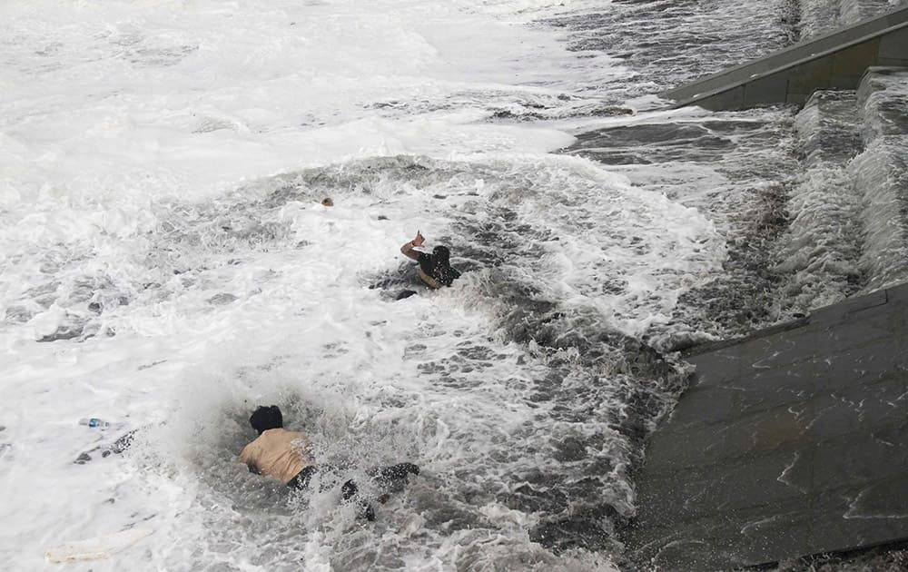 A man, bottom jumps into the water to rescue a woman, center, who fell due to strong tidal waves on the Bay of Bengal coast at Gopalpur, Orissa, about 285 kilometers (178 miles) north east of Visakhapatnam, India.