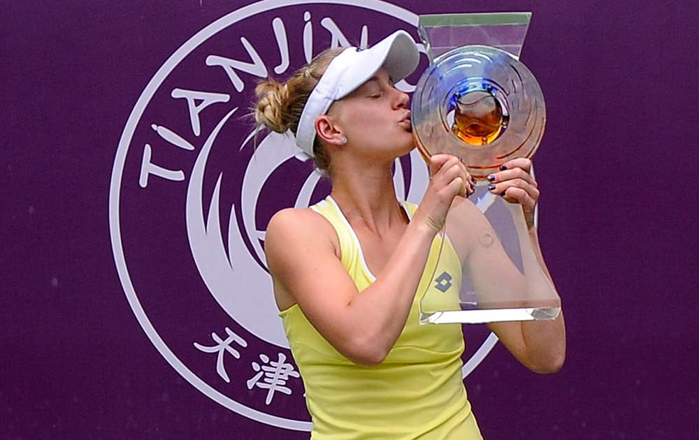 Alison Riske of the United States kisses her trophy after defeating Belinda Bencic of Switzerland for the women's singles final at the Tianjin Open tennis tournament in Tianjin, northern China.