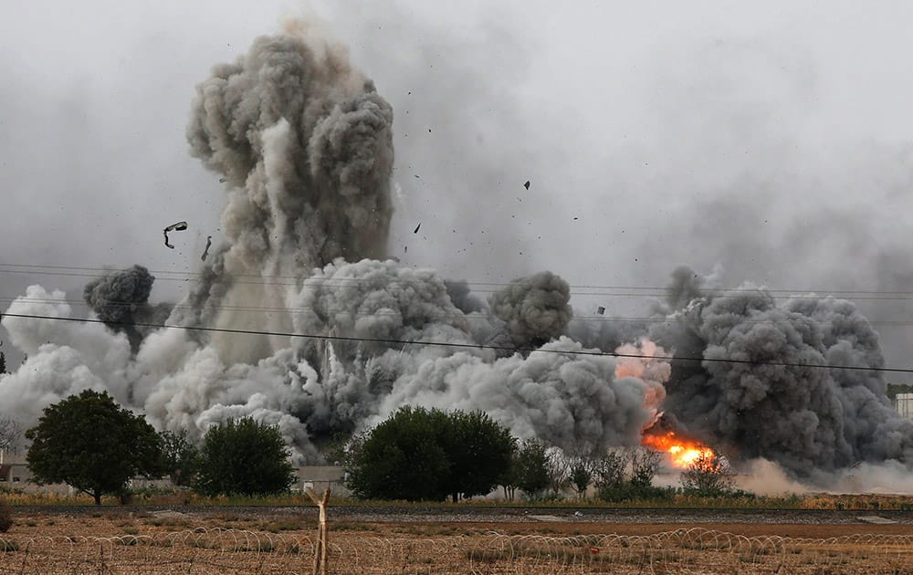 Thick smoke, debris and fire rise following an airstrike by the US-led coalition in Kobani, Syria as fighting intensified between Syrian Kurds and the militants of Islamic State group, as seen from Mursitpinar on the outskirts of Suruc, at the Turkey-Syria border.