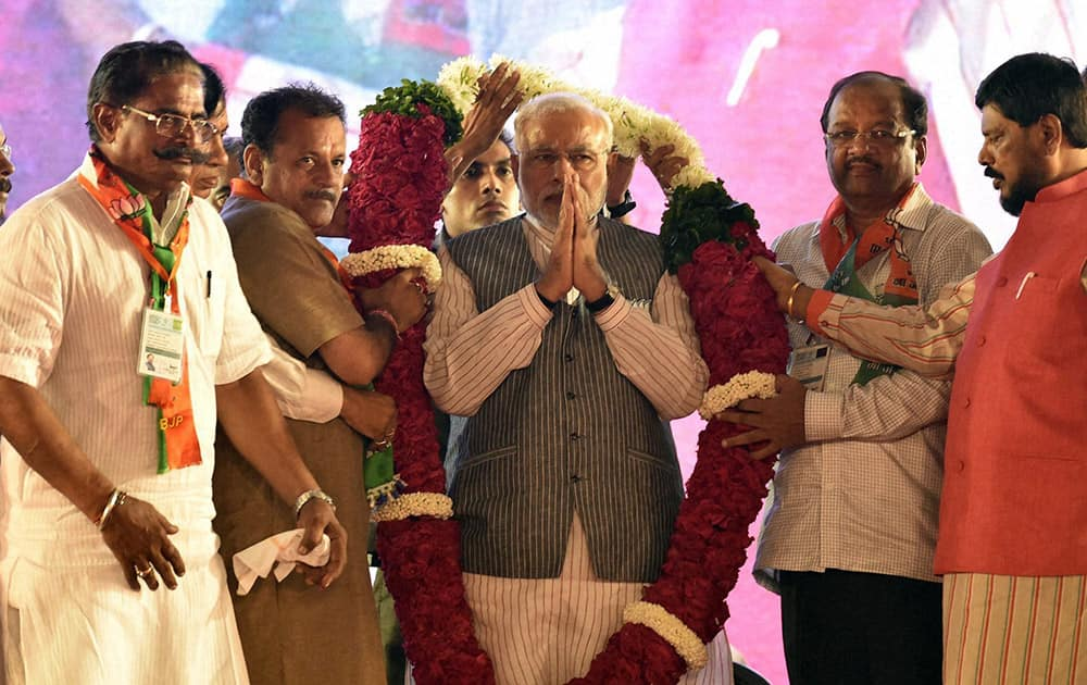 Prime Minister Narendra Modi is garlanded during an election campaign rally at Borivali in Mumbai.