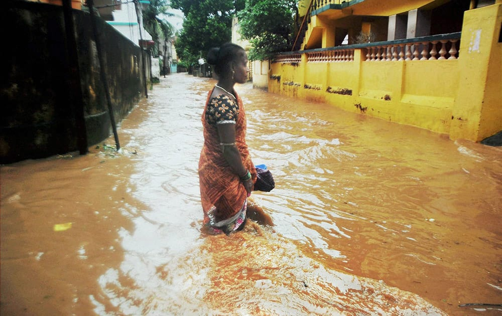 A woman wades through a water logged street after cyclone Hudhud caused heavy rains in Bhubaneswar.