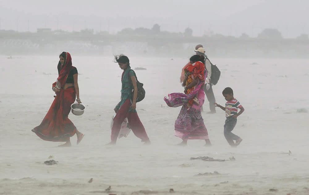 People walk through a dust storm on the bank of river Ganga in Allahabad.