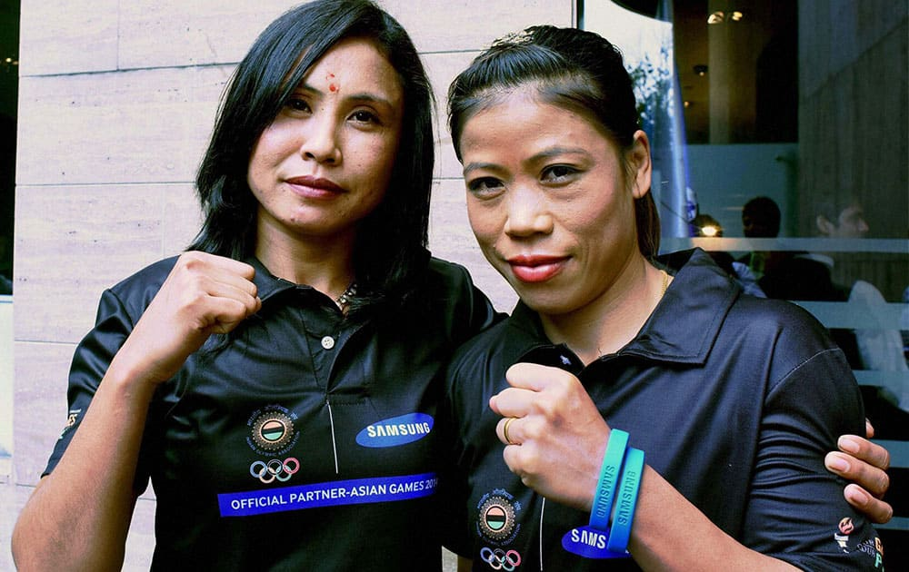 Boxers Mary Kom and L Sarita Devi pose for photographs during a felicitation function organised by Samsung for the medal winners of recent Asian Games, in New Delhi.