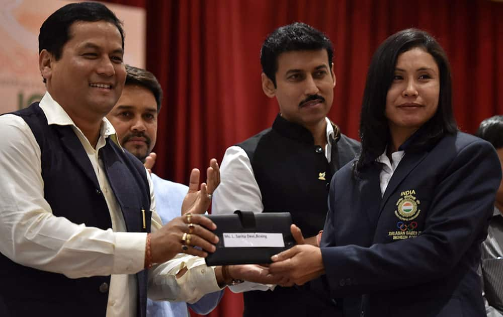 Union Minister of State (I/C) for Skill Development, Youth Affairs & Sports Sarbananda Sonowal felicitates boxer L Sarita Devi during a felicitation ceremony for the 17th Asian Games Medalist in New Delhi.