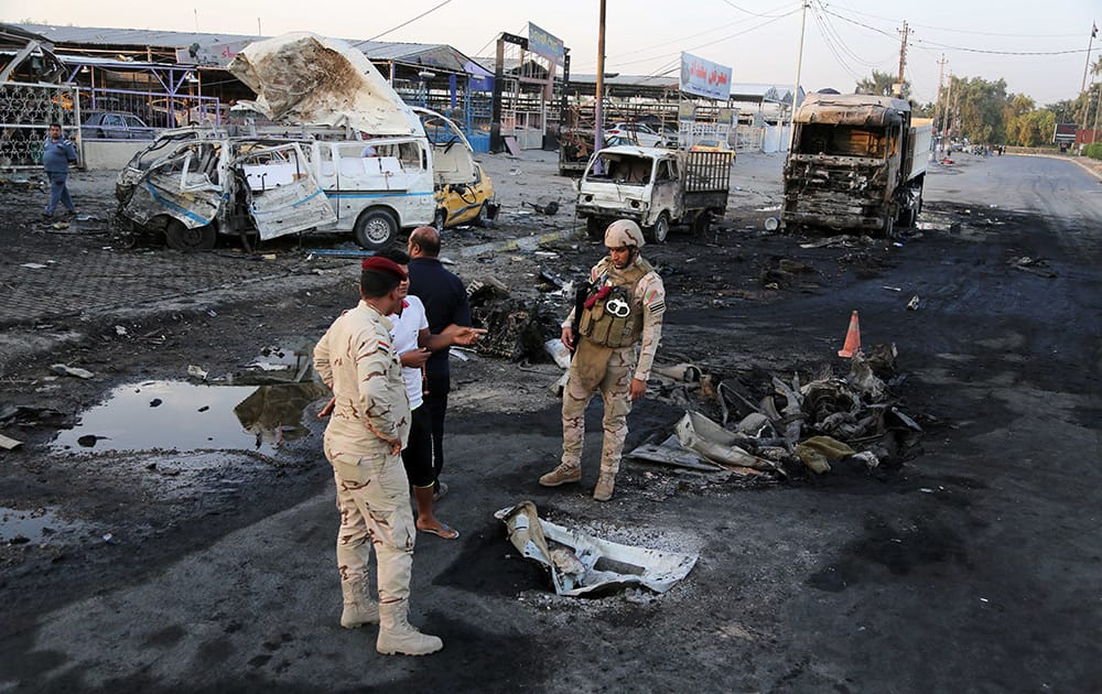 Security forces and civilians inspect the aftermath of a Monday car bombing, in the eastern Habibiya district of Baghdad, Iraq.