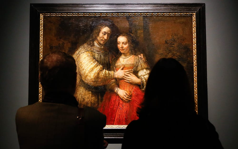 People look at Rembrandt's painting Portrait of a Couple as Isaac and Rebecca, known as 'The Jewish Bride' about 1665 during a media event at The National Gallery in London.