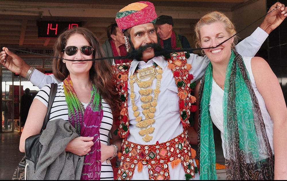 Tourists pose with a Rajasthani artist on their arrival by Maharaja Express train in Bikaner.