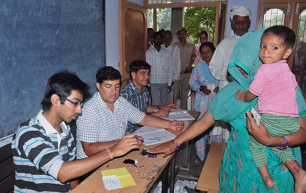 People arrive to cast votes for Assembly polls, at a polling station in Sonipat.