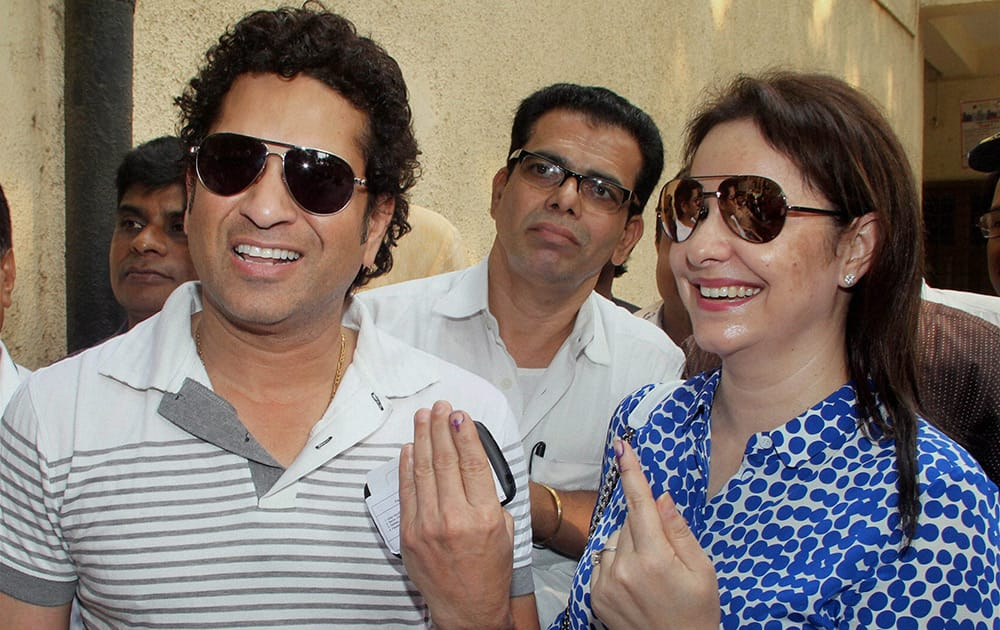 Cricket legend Sachin Tendulkar and his wife Anjali display their inked fingers after casting votes for the Assembly elections in Mumbai.