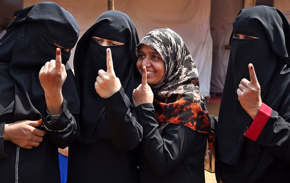 Muslim women show the ink mark on their index fingers after casting their votes to the Maharashtra state elections in Mumbai.