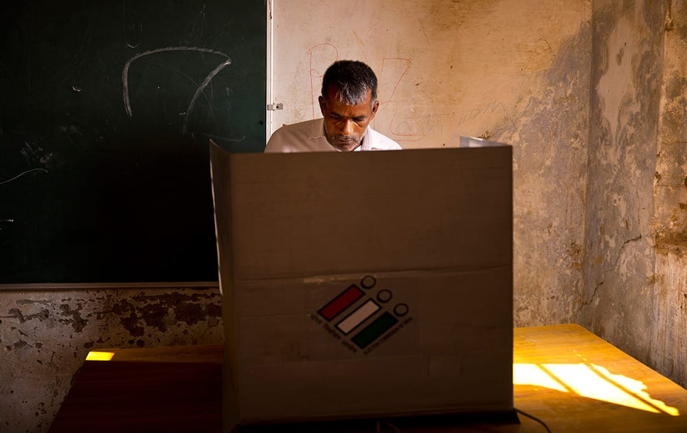 A man casts his vote during the Haryana state elections in Gwalpur Pahari.