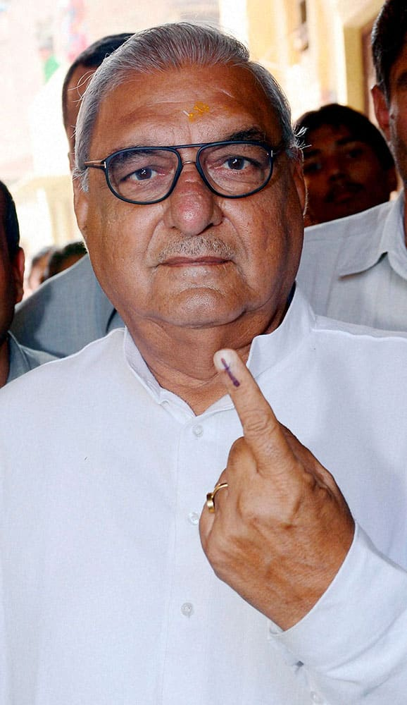 Haryana CM Bhupinder Singh Hooda shows his inked finger after casting his vote for the Assembly polls at a polling booth in Rohtak on Wednesday.