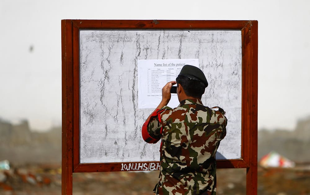 A Nepalese army soldier takes a photo of a patient's list at the Army hospital in Katmandu, Nepal. At least 14 foreign trekkers have been rescued so far, including two from Hong Kong and 12 Israelis who were being treated at the Military Hospital in Katmandu.