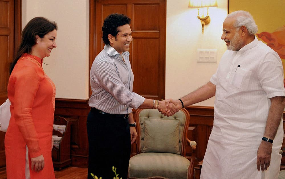 Prime Minister Narendra Modi shakes hands with cricket legend Sachin Tendulkar as his wife Anjali looks on at a meeting in New Delhi.