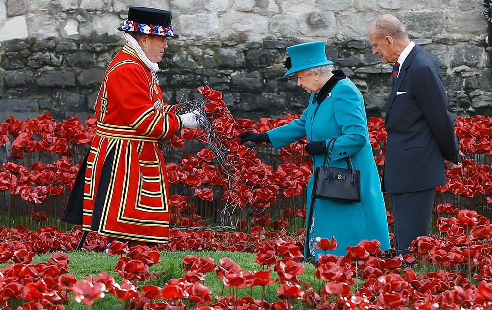 Britain's Queen Elizabeth II, alongside the Duke of Edinburgh, touches a wreath held by a Yeoman Warder before it is laid in the field of ceramic poppies at The Tower of London.