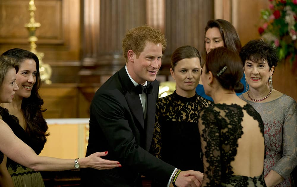 Britain's Prince Harry, greets members of the 100 Women in Hedge Funds Philanthropic Initiatives prior to a group photograph taken for their gala dinner in aid of the Well Child charity at the Royal Hospital Chelsea, in London.