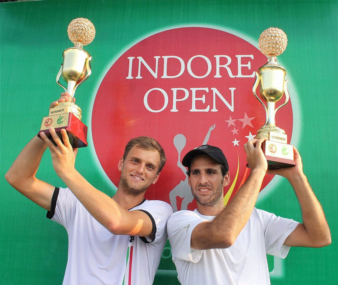Aleksandr Nedovyesov of Kazakhstan with Adrian Menendez-Maceiras of Spain showing their trophies after winning the final match against Indias Yuki Bhambri and Divij Sharan at Indore Open ATP challenger tennis tournament, in Indore.
