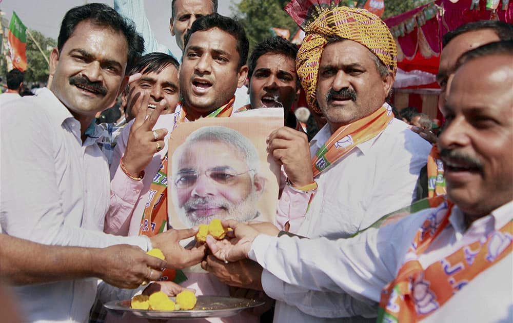 BJP workers offer sweets to a poster of PM Narendra Modi while celebrating the party victory in the Assembly polls in Gurgaon.